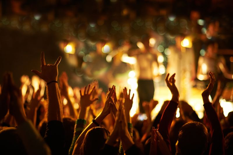 Audience with hands raised at a music festival and lights streaming down from above the stage