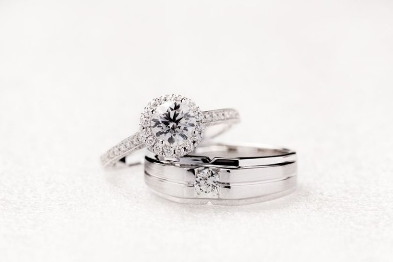 Bride and groom wedding engagement rings on white background