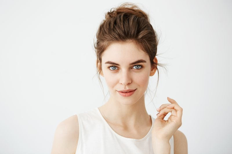 Portrait of young beautiful playful girl with bun looking at camera posing over white background