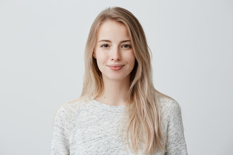 Pretty smiling joyfully female with fair hair, dressed casually, looking with satisfaction at camera, being happy. Studio shot of good-looking beautiful woman isolated against blank studio wall