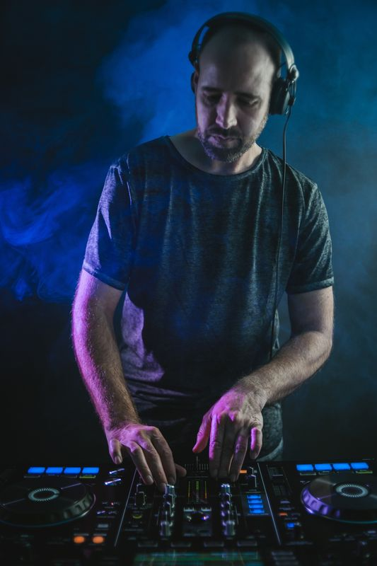 Vertical picture of a Male DJ under the blue lights and smoke in a studio