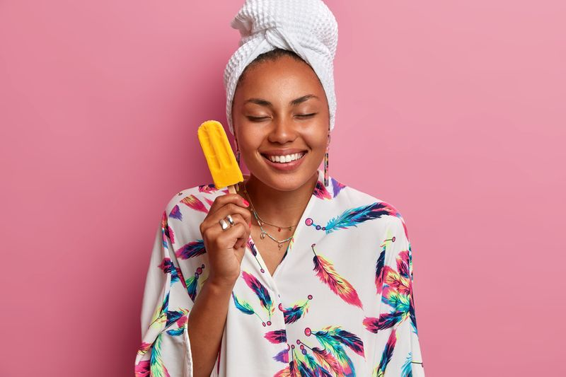 Photo of happy healthy woman with dark skin closes eyes and smiles pleasantly holds delicious ice cream with mango flavor wears domestic robe wrapped towel on head poses over rosy studio wall