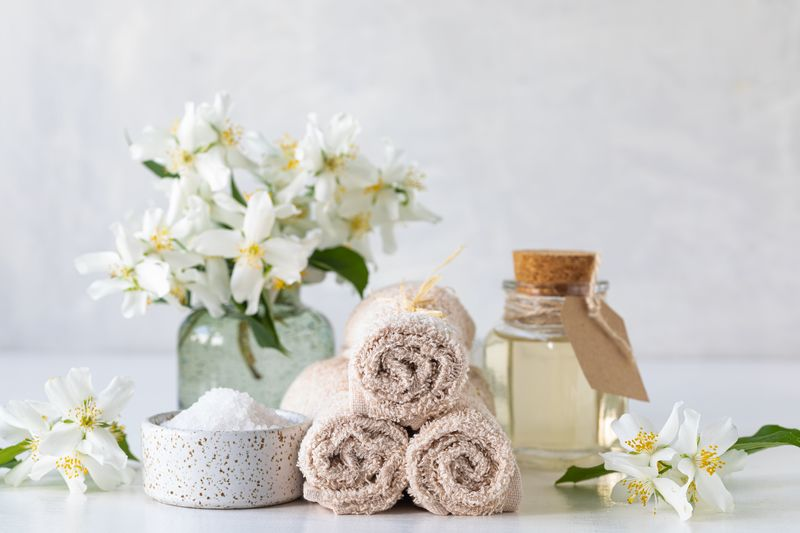 Spa concept of jasmine oil, with bath salt and flowers on a white background. Spa and wellness still life. Copy space
