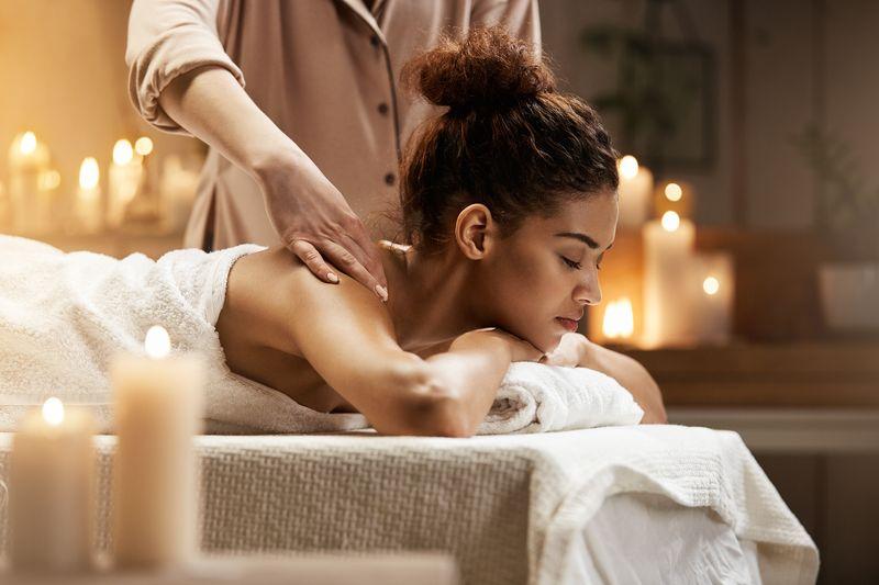 Tender african girl smiling enjoying massage with closed eyes in spa resort