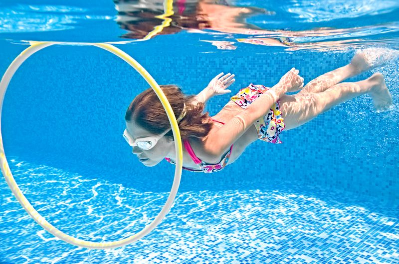 child-swims-underwater-swimming-pool-little-active-girl-dives-has-fun-water