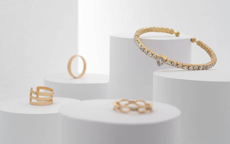 Beautiful precious bracelet with diamonds and rings collection on white platforms