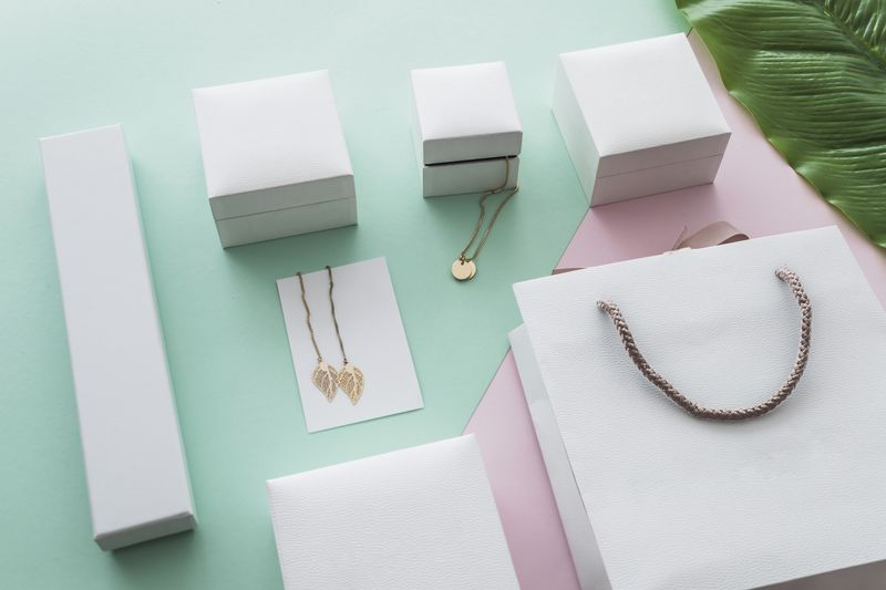 golden-jewelry-boxes-with-shopping-bag-pastel-background