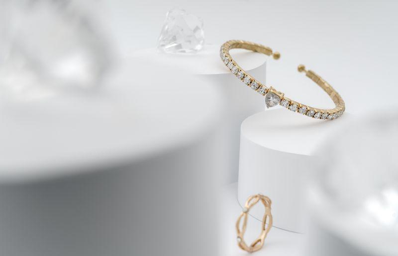 Golden with diamonds bracelet between diamonds on white platform