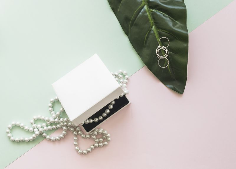 overhead-view-pearl-necklace-white-box-rings-leaf-pastel-background(1)